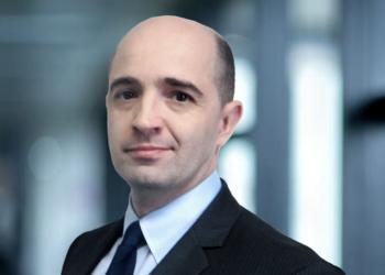 Um homem sorri de lado, vestindo terno e gravata. TozziniFreire Congresso dos Advogados Trabalhistas