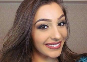 Uma mulher jovem e maquiada sorri.