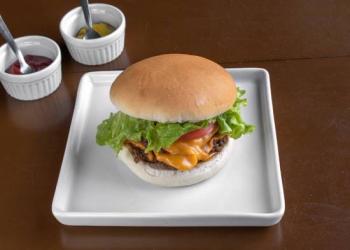 Hambúrguer em um pratinho quadrado e dois recipientes de molho.