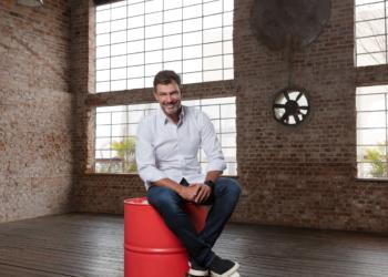 Dado Bier. Empresário. Um homem sentado em cima de um tonel vermelho.