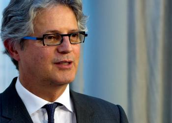 Futuro do Trabalho: o palestrante, um homem de óculos, terno e gravata, olha para o infinito levemente de perfil.