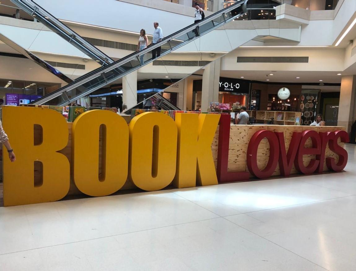 Feira literária. Letreiro Book Lovers. Atrás, pessoas em escadas rolantes.