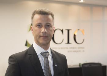 Turismo e crescimento. Um homem de gravata em frente a uma parede onde se lê CIC.