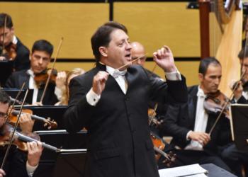 Ospa. Maestro, em primeiro plano, rege orquestra à sua volta