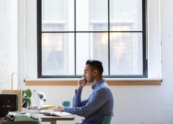 Endeavor. Um homem trabalha em casa, uma mesa de trabalho e janela atrás.