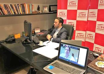 Marchezan aparece em uma tela de notebook enquanto outra pessoa, o presidente do LIDE.