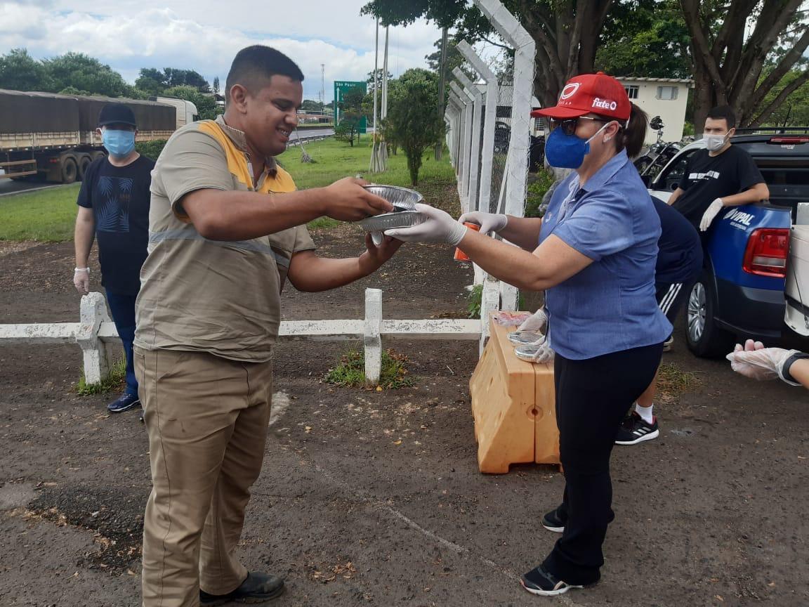 Vipal. Pessoas com máscaras entregam suprimentos a um caminhoneiro.