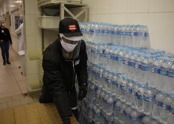 Coca-Cola, doação de água. Um homem usa máscara e separa garrafas de água.
