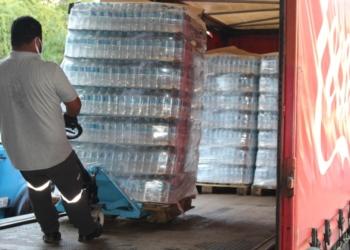 Coca-Cola, caminhão com garrafas de água. Um homem desloca garrafas em um carrinho.