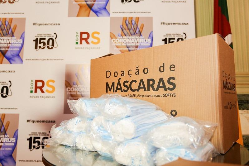 CMPC caixa com doação de máscaras e logos do governo ao fundo
