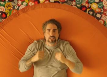 Um homem deitado em uma superfície laranja.