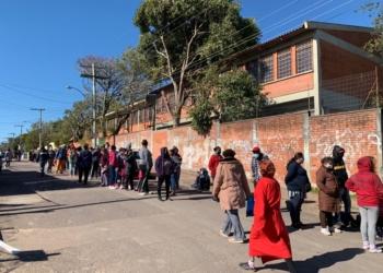 Parceiros Voluntários intermediou doação. Fila de pessoas ao lado de um muro de tijolos.