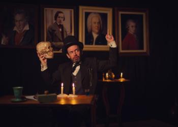 Arte Sesc Em Casa Com Você - um homem com terno preto, cartola, segura uma caveira na mão. Atrás, quadros. Ambiente escuro, iluminado com velas.