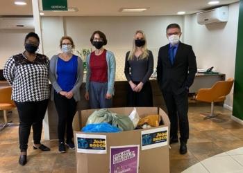 Unicred. Caixa de doações com colaboradores usando máscaras atrás.