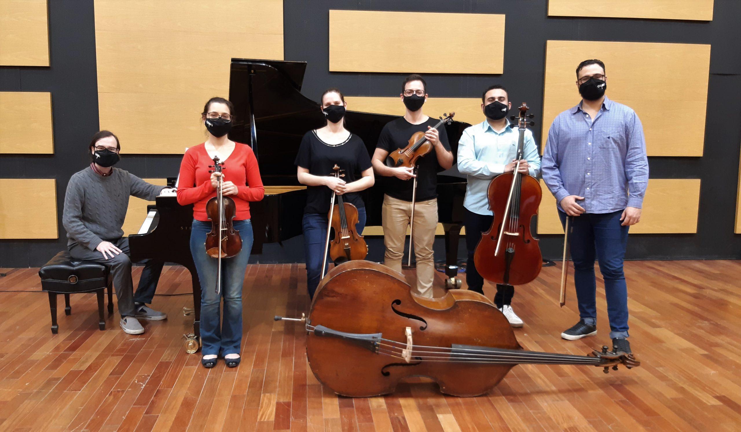Músicos no palco da OSPA, com seus instrumentos: piano, violino, violoncelo, contrabaixo, todos de máscara.