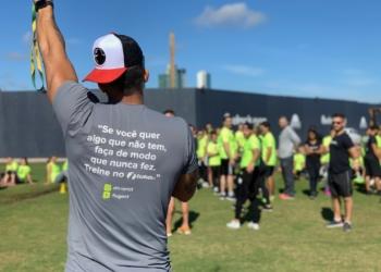 """Lugo CT. Profissional de educação física com uma camiseta em que se lê """"Se você quer algo que não tem, faça de modo que nunca fez. Treine no Lugo CT"""". Ao fundo se vê, de forma desfocada, mais pessoas."""