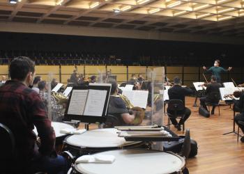 Orquestra no palco, com instrumentos musicais, máscaras e uma divisória transparente entre eles.