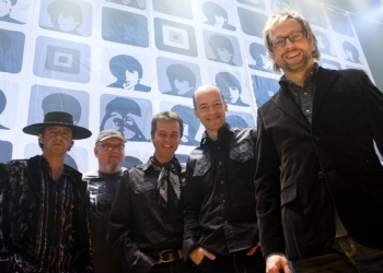 Banda Nenhum de Nós canta Beatles. Músicos em frente a painel com o quarteto britânico.