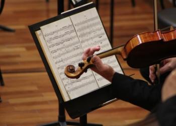 Mozart e Dvořák; partitura e braço de uma pessoa tocando violino.