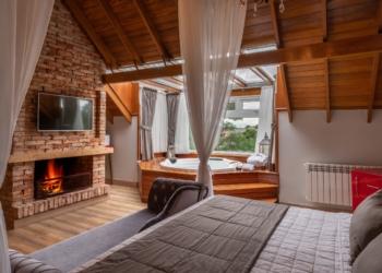 Valle D'incanto Midscale Hotel, vista de um quarto onde se vê cama de casal, lareira, banheira spa e janela e teto de vidro.