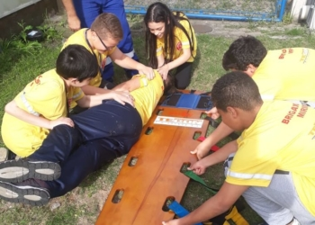 Crianças em volta de uma prancha para primeiros-socorros durante treinamento de atendimento a uma pessoa deitada.