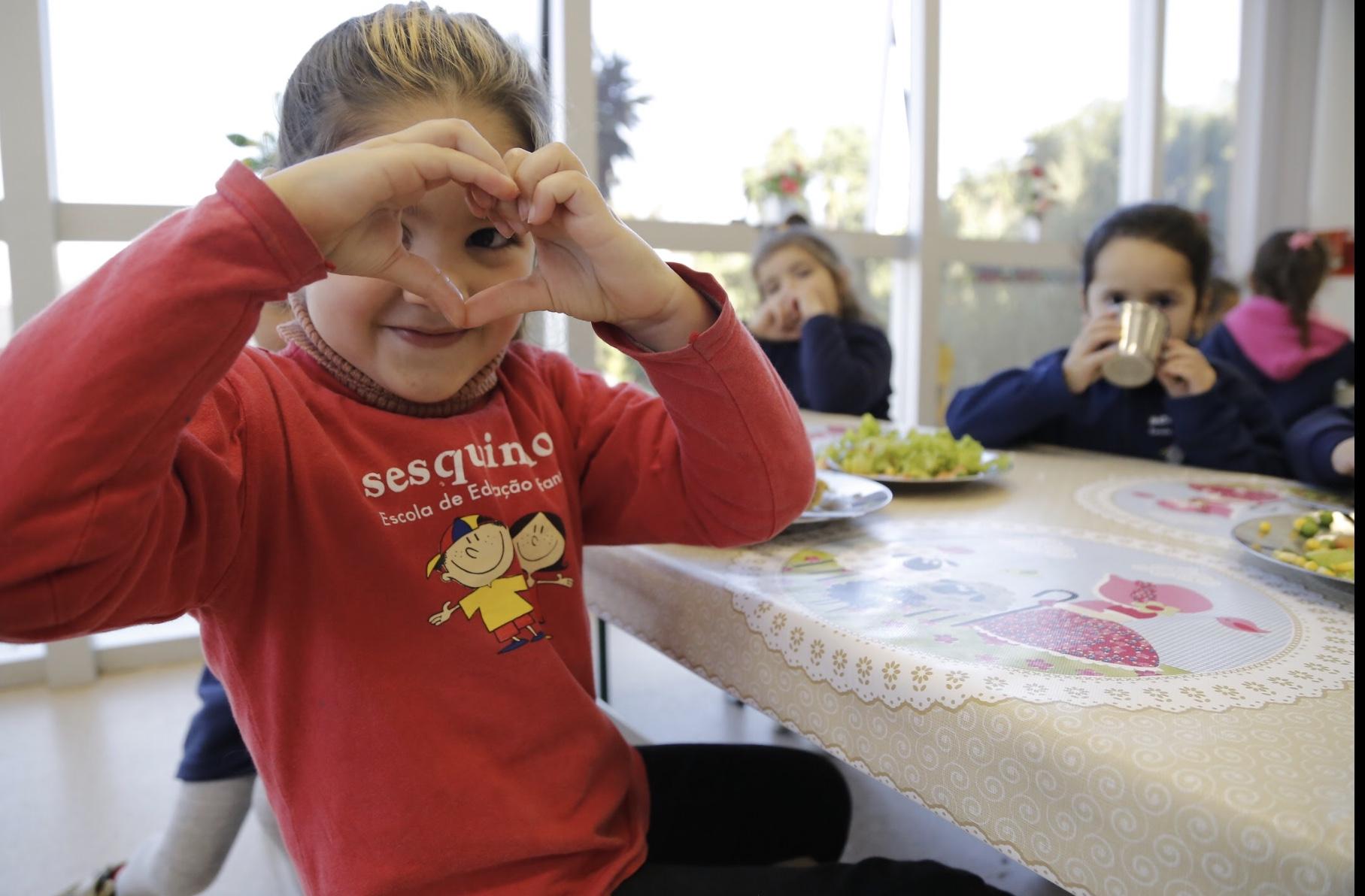 Sesc escola infantil e crianças. Uma delas faz sinal de coração.