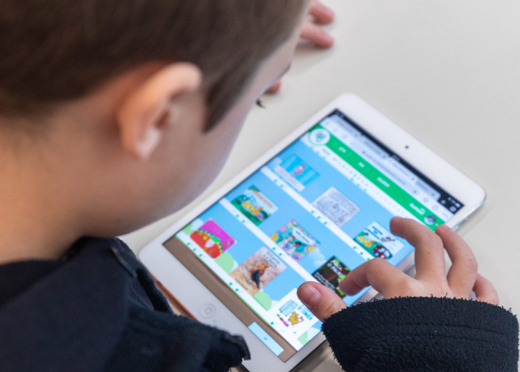 Menino lê em um tablet da Elefante Letrado.