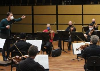 Maestro conduz músicos em ensaio.