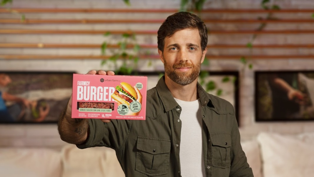 """Um homem vestindo camiseta branca e camisa marrom por cima segura uma caixa onde se lê em destaque """"Farmcy BURGER""""."""
