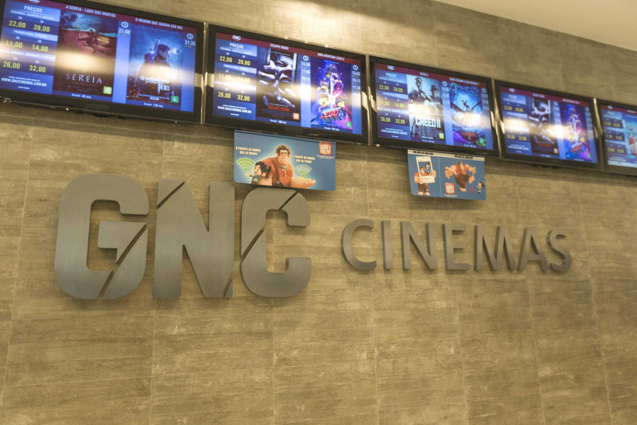 GNC Cinemas escrito na parede e acima tvs com a programação.