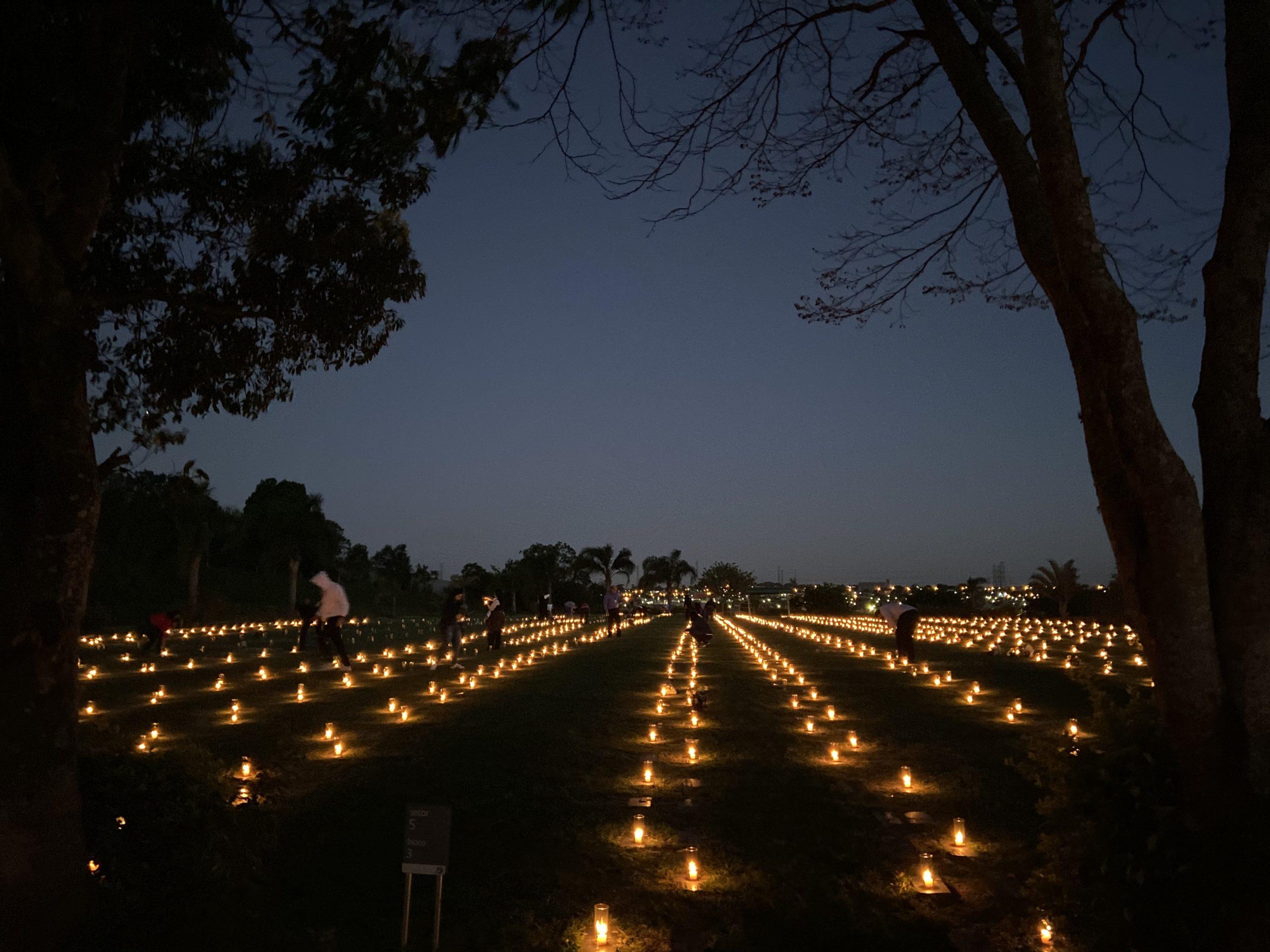 Várias velas acesas à noite em um campo com as pessoas circulando por ele.
