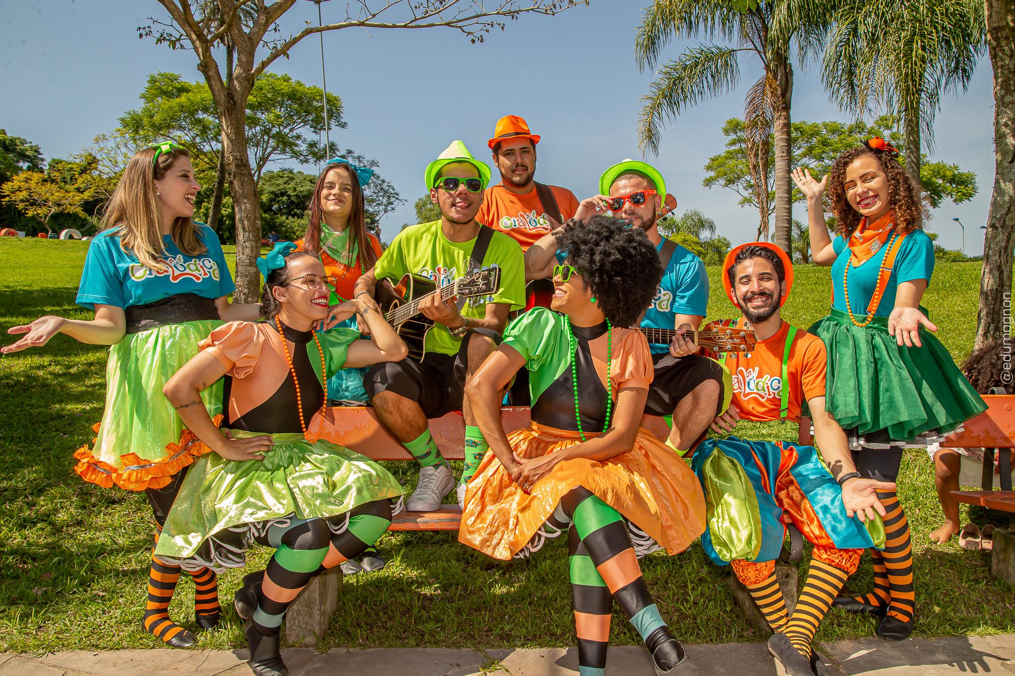 Dia da Criança terá Cia. Lúdica. Nove pessoas, entre homens em mulheres, com roupas coloridas em um dia ensolardo, com muito verde em volta. Dois homens estão com dois violões, e todos sorriem.