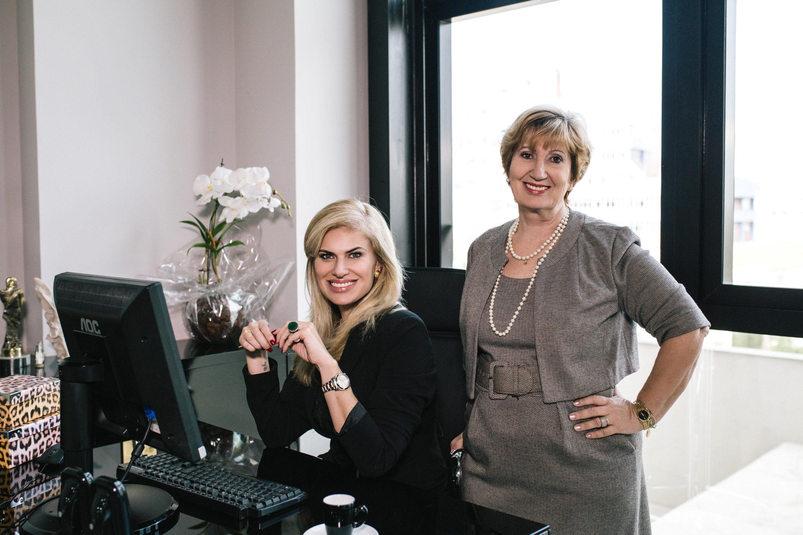 Uma mulher sentada e outra em pé em frente a uma mesa de escritório, com flores atrás. A que está sentada é mais jovem.