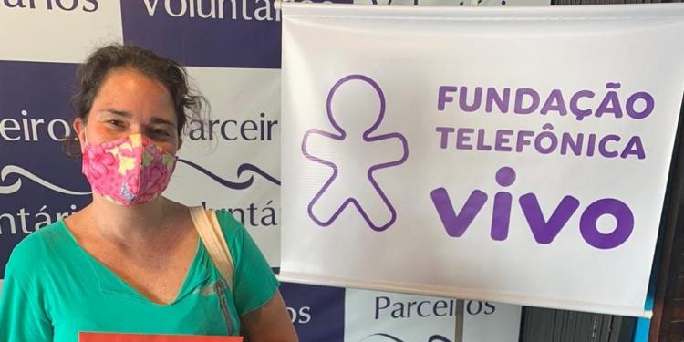Mulher segura envelope ao lado de uma faixa da Fundação Telefônica Vivo e em frente a um banner da ong Parceiros Voluntários.