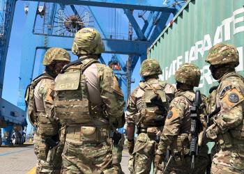 Militares participam de simulação de segurança portuária. Homens vestidos com roupas do exército em um porto num dia de céu azul.