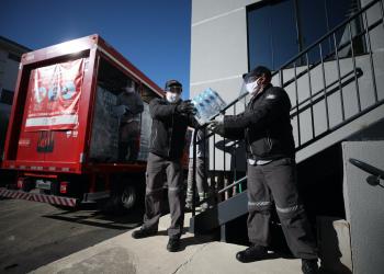 Dois homens carregam caminhão da Coca-Cola.