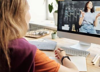 Mulher jovem assiste aula online onde outra mulher aparece na tela.