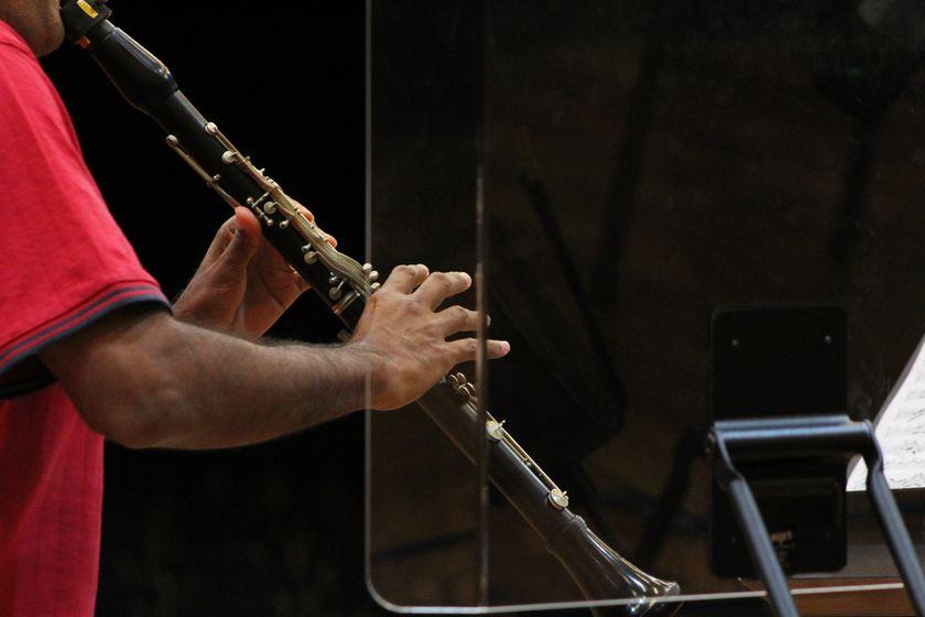 Braços seguram um clarinete.