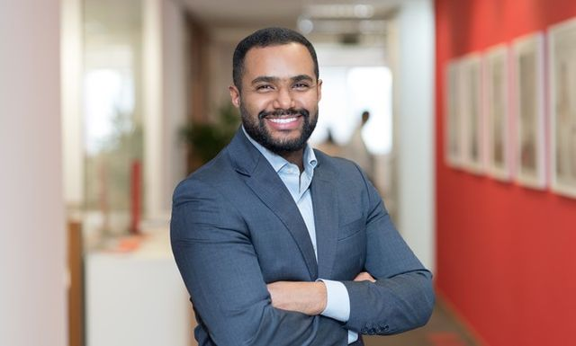 Homem negro, de barba, de terno, sorri para a câmera de braços cruzados.