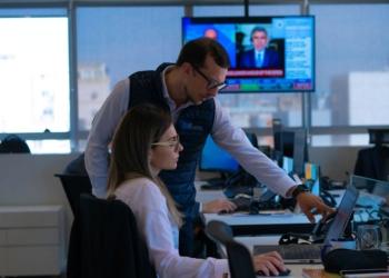 Um homem e uma mulher olham para uma tela de computador. Ao fundo, notícias na tv.