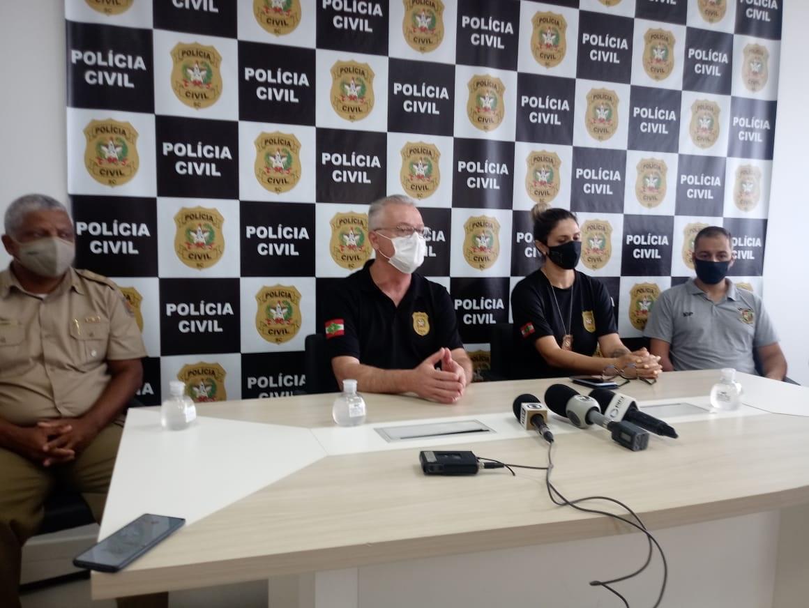 Coletiva de imprensa com quatro policiais explicando as ações realizadas para encontrar a menina Fabíola. Eles estão sentados junto a uma mesa, onde estão postos microfones. Ao fundo, um painel com o brasão da Polícia Civil de Santa Catarina.