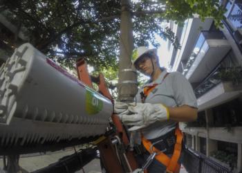 Mulher usando equipamentos de segurança faz instalação de equipamentos da Oi em poste.