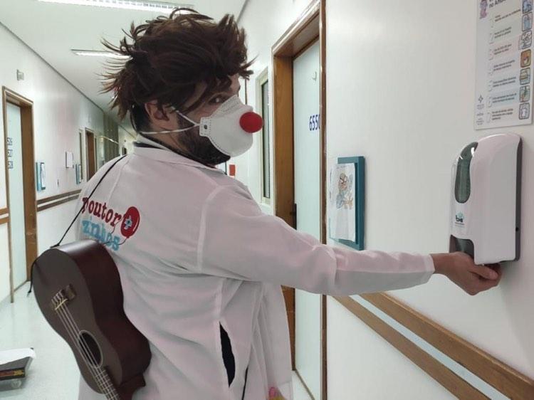Doutorzinhos: um homem vestido com um jaleco que, nas costas, traz o nome do projeto; ele carrega nas costas um cavaquinho, e usa máscara com nariz de palhaço. Ele aciona um dispositivo de álcool gel.