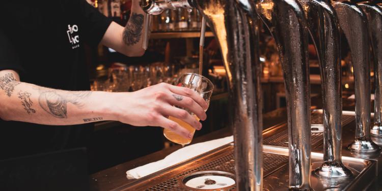 Cervejeiro. Uma mão segura um copo e outra abre uma torneira de cerveja.